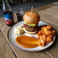 Vegan chorizo-style burger, home-smoked tomato ketchup, coleslaw, relish, paprika crisps, and a Karma Cola at West Six Garden Cafe in West London